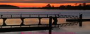 sunset over a dock with a sloping ramp from shore