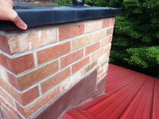 Home and cottage inspection in muskoka, Gravenhurst, Bracebridge, Balla, Port Carling and Huntsville includes roofing inspections where we walk most roofs to get the most detailed inspection possible. Here our inspector is checking a chimney cap and flashing. Inspector is on roof looking at flashing around chimney